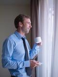 Кофе бизнесмена выпивая, смотря из окна Стоковая Фотография