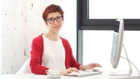 Кофе бизнесмена молодой женщины выпивая в рабочем месте сток-видео