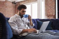 Кофе бизнесмена работая и выпивая на софе в офисе Стоковое Изображение RF