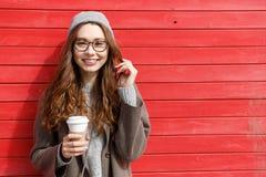 Кофе взятия жизнерадостной милой молодой женщины выпивая отсутствующий Стоковые Изображения