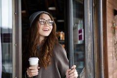 Кофе взятия жизнерадостной симпатичной молодой женщины выпивая отсутствующий Стоковая Фотография RF