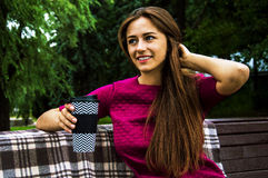 Кофе восхитительной девушки выпивая в парке сидя на стенде Стоковые Фотографии RF
