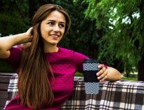 Кофе восхитительной девушки выпивая в парке сидя на стенде стоковое фото rf