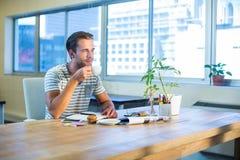 Кофе вскользь бизнесмена выпивая на его столе Стоковое фото RF
