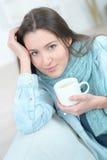 Кофе выпивая чашки женщины на софе Стоковые Фото