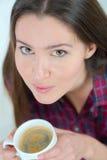 Кофе выпивая чашки женщины на софе Стоковое фото RF