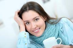 Кофе выпивая чашки женщины на софе Стоковая Фотография RF