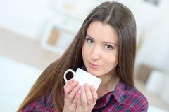 Кофе выпивая чашки женщины на софе Стоковые Изображения