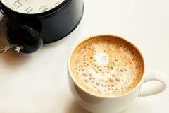 Кофе в белой чашке с красивой пеной и черным будильником Стоковые Фото