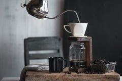 Кофе в стеклянной бутылке, потек кофе, рука держа кофе потека чайника в комнате Стоковое Изображение RF