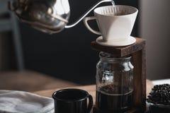 Кофе в стеклянной бутылке, потек кофе, рука держа кофе потека чайника в комнате Стоковое фото RF