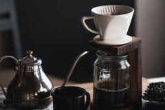 Кофе в стеклянной бутылке, потек кофе, рука держа кофе потека чайника в комнате Стоковые Фото