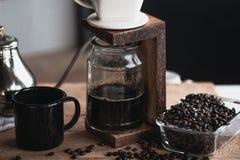 Кофе в стеклянной бутылке, потек кофе, рука держа кофе потека чайника в комнате Стоковая Фотография
