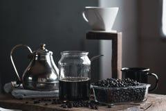 Кофе в стеклянной бутылке, потек кофе, рука держа кофе потека чайника в комнате Стоковые Фотографии RF