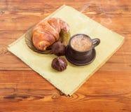 Кофе в черных керамических трюфелях чашки, круассана и шоколада Стоковая Фотография