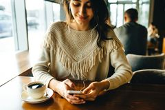 Кофе девушки выпивая и слушать к музыке в кафе стоковые изображения rf