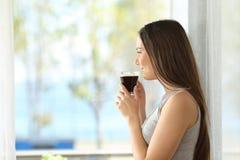 Кофе девушки выпивая смотря через окно Стоковая Фотография