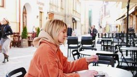 Кофе женщины выпивая в кафе Занятый городской транспорт за окном ЗАМЕДЛЕННОЕ ДВИЖЕНИЕ 4K DCi Девушка наслаждаясь горячим напитком видеоматериал