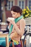 Кофе женщины выпивая в кафе на улицах Стоковая Фотография RF