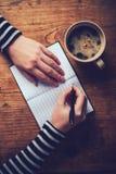 Кофе женщины выпивая и запись примечания дневника Стоковые Изображения