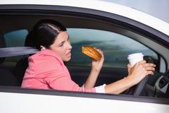 Кофе женщины выпивая и сандвич еды на телефоне Стоковая Фотография