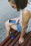 Кофе женщины выпивая и смотреть телефон Стоковая Фотография