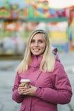 Кофе женщины выпивая на предпосылке парка атракционов Стоковая Фотография RF