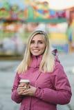 Кофе женщины выпивая на предпосылке парка атракционов Стоковое Изображение RF