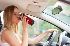 Кофе женщины выпивая пока управляющ ее автомобилем Стоковое фото RF