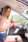 Кофе женщины выпивая пока управляющ ее автомобилем Стоковое Изображение