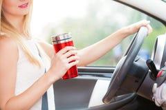 Кофе женщины выпивая пока управляющ ее автомобилем Стоковые Фото