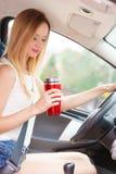 Кофе женщины выпивая пока управляющ ее автомобилем Стоковое Изображение RF