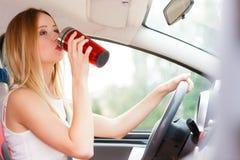 Кофе женщины выпивая пока управляющ ее автомобилем Стоковая Фотография RF