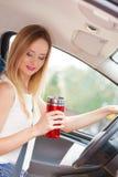 Кофе женщины выпивая пока управляющ ее автомобилем Стоковые Фотографии RF