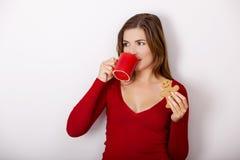 Кофе женщины выпивая с печеньями Стоковые Изображения