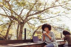 Кофе женщины выпивая outdoors Стоковые Изображения