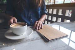 Кофе женщины держа и выпивая с тетрадью на таблице в кафе Стоковая Фотография