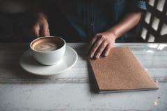 Кофе женщины держа и выпивая с тетрадью на таблице в кафе Стоковая Фотография RF
