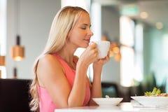 Кофе женщины есть и выпивая на ресторане Стоковые Изображения