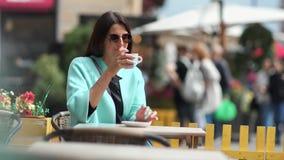 Кофе жизнерадостной модной туристской женщины выпивая на на открытом воздухе кафе усмехаясь и ослабляя среднюю съемку видеоматериал