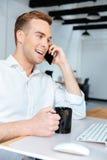 Кофе жизнерадостного бизнесмена выпивая и говорить на мобильном телефоне Стоковое фото RF