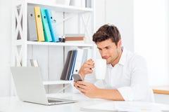 Кофе жизнерадостного молодого бизнесмена выпивая и говорить на мобильном телефоне Стоковое Фото
