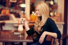 Кофе жизнерадостной девушки выпивая в кафе Стоковое Изображение
