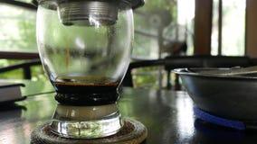 Кофе заваривать с молоком используя въетнамский традиционный фильтр phin в кафе Потеки кофе медленно падают в стеклянную чашку видеоматериал