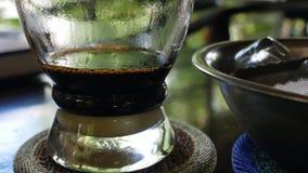 Кофе заваривать с молоком используя въетнамский традиционный фильтр phin в кафе Потеки кофе медленно падают в стеклянную чашку акции видеоматериалы