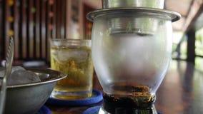 Кофе заваривать черный используя въетнамский традиционный фильтр phin в кафе Потеки кофе медленно падают в стеклянную чашку Ca акции видеоматериалы