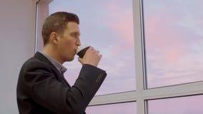 Кофе задумчивого молодого бизнесмена выпивая и смотреть вне из окна в офисе сток-видео