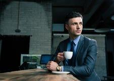 Кофе задумчивого бизнесмена выпивая в кафе Стоковое Изображение