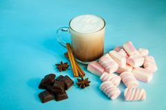 Кофе или шоколад какао питья рождества горячие с сливк и зефирами молока в малой прозрачной чашке на голубой предпосылке Стоковые Изображения