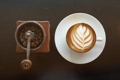 Кофе искусства поздно с кофейным зерном внутри мельницы руки стоковая фотография